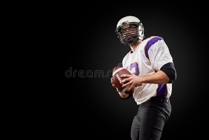 Jugador del deportista del fútbol americano en fondo negro Concepto del deporte imagen de archivo libre de regalías