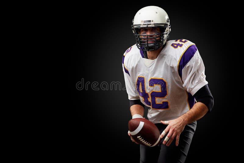 Jugador del deportista del fútbol americano en fondo negro Concepto del deporte fotos de archivo