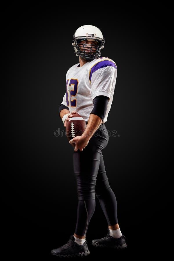 Jugador del deportista del fútbol americano en fondo negro Concepto del deporte foto de archivo