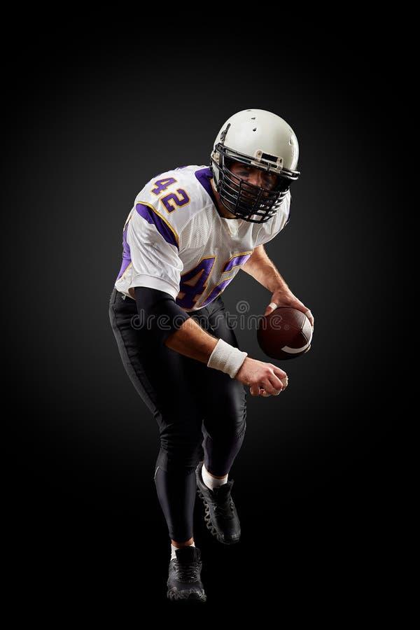 Jugador del deportista del fútbol americano en fondo negro Concepto del deporte fotos de archivo libres de regalías