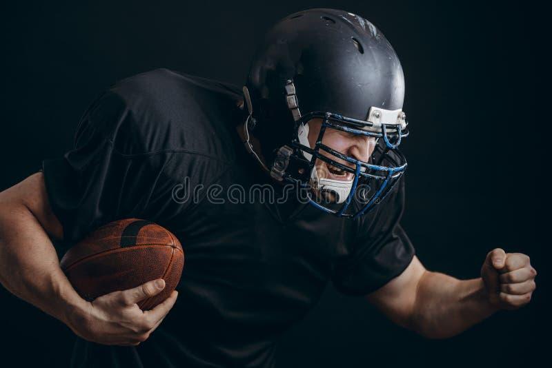Jugador del deportista del fútbol americano en la acción aislado sobre la pared negra del estudio imagen de archivo