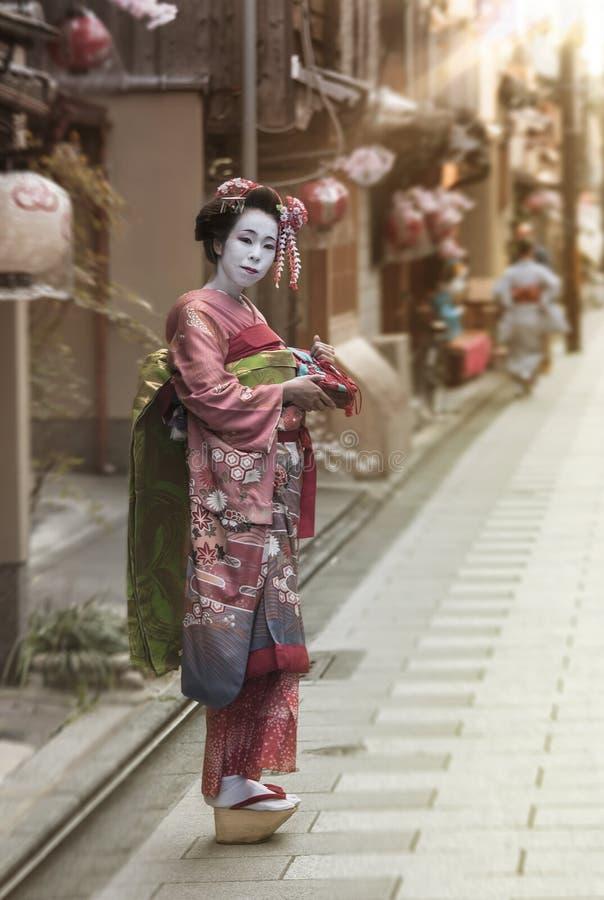 Jugador del geisha o del traje del maiko que camina en un callejón de Kyoto en la luz de la puesta del sol foto de archivo libre de regalías