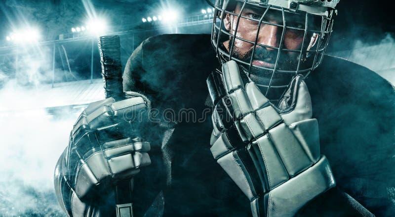 Jugador del hockey sobre hielo en el casco y guantes en estadio con el palillo fotografía de archivo