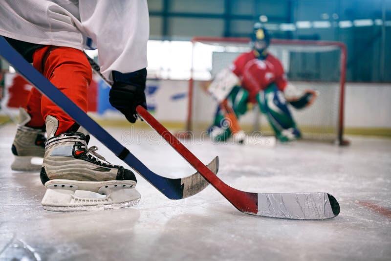 Jugador del hockey sobre hielo en la acción que golpea con el pie con el palillo fotos de archivo