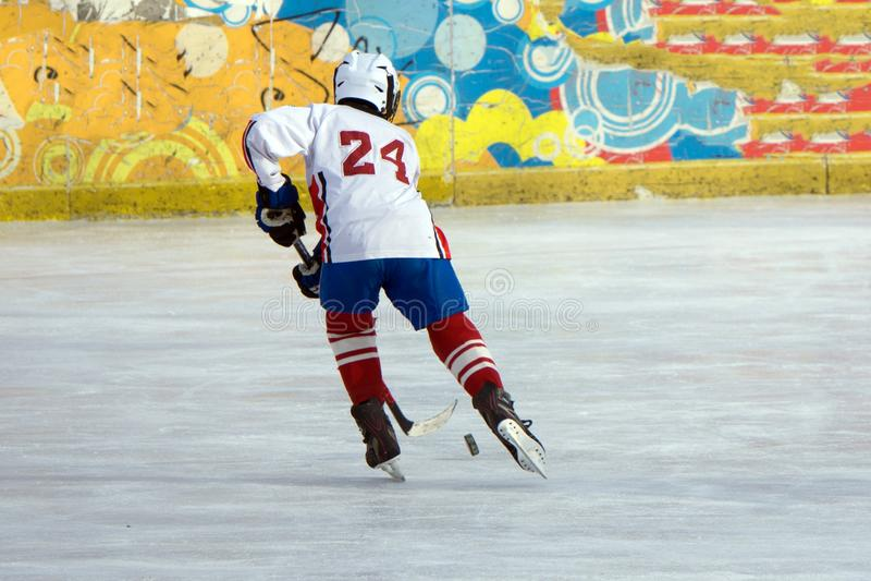 Jugador del hockey sobre hielo en la acción que golpea con el pie con el palillo foto de archivo libre de regalías