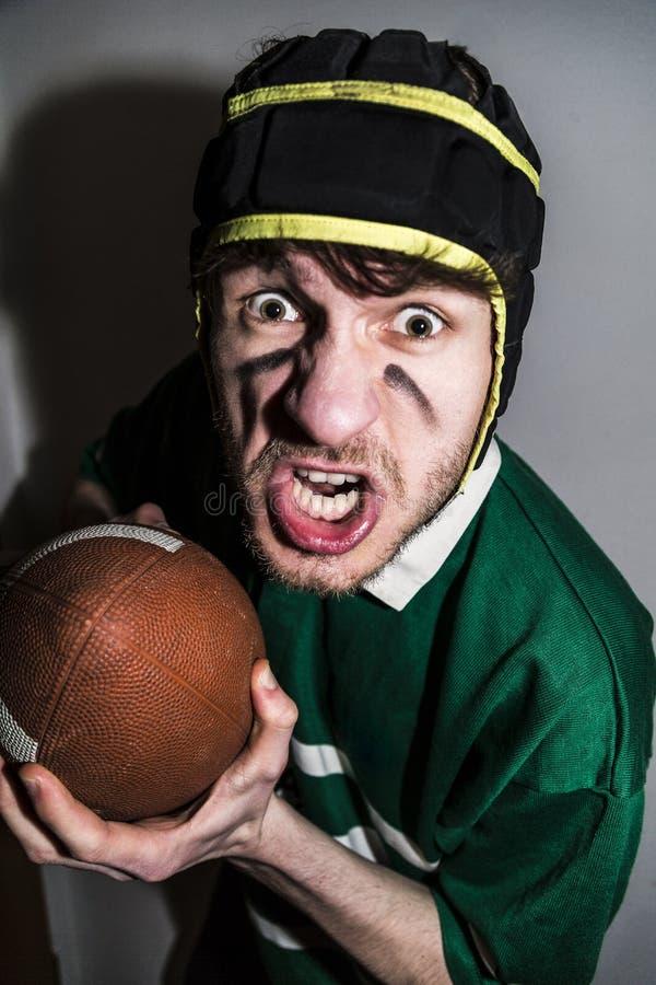 Jugador del rugbi con la bola en las manos que hacen la cara torcida fotografía de archivo