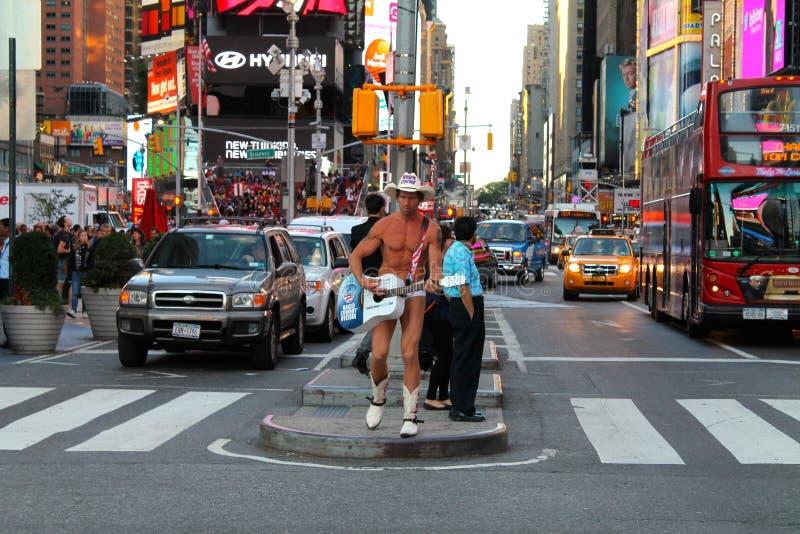 Jugador desnudo de Guitar del vaquero en la calle de Manhattan, cuadrado del tiempo, New York City, los E.E.U.U. foto de archivo