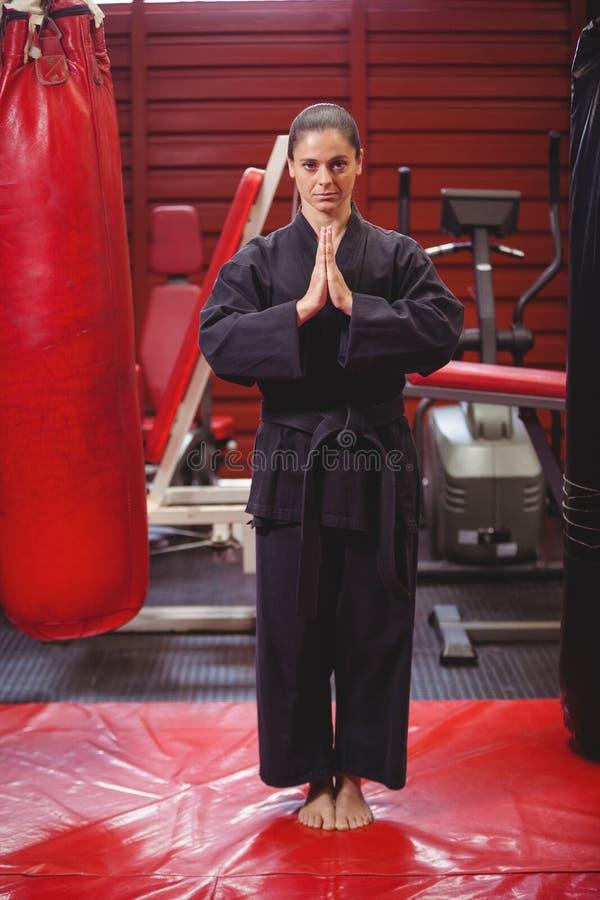 Jugador femenino del karate que realiza postura del karate imagen de archivo