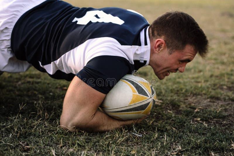 Jugador fuerte del rugbi con la bola en la tierra foto de archivo libre de regalías
