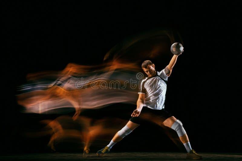 Jugador joven del balonmano contra fondo oscuro del estudio en luz mezclada imagen de archivo