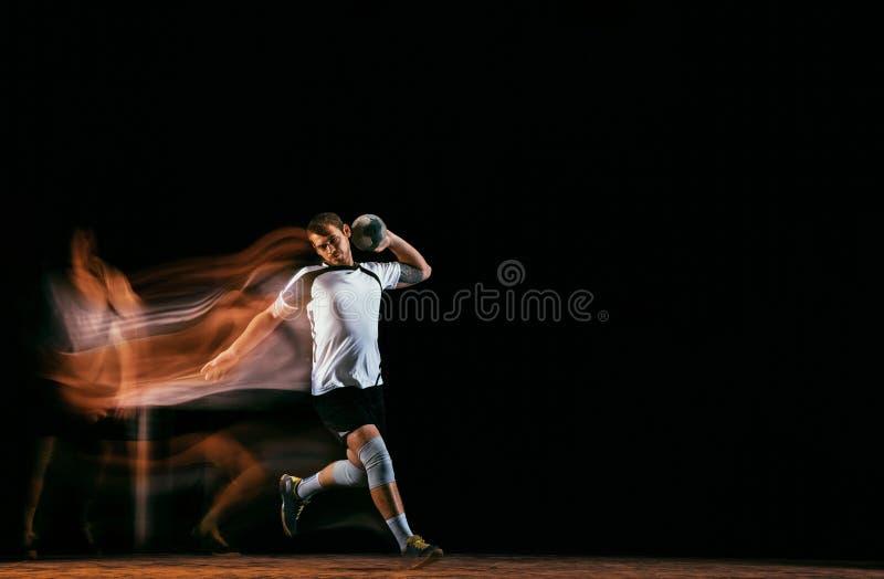 Jugador joven del balonmano contra fondo oscuro del estudio en luz mezclada fotos de archivo libres de regalías