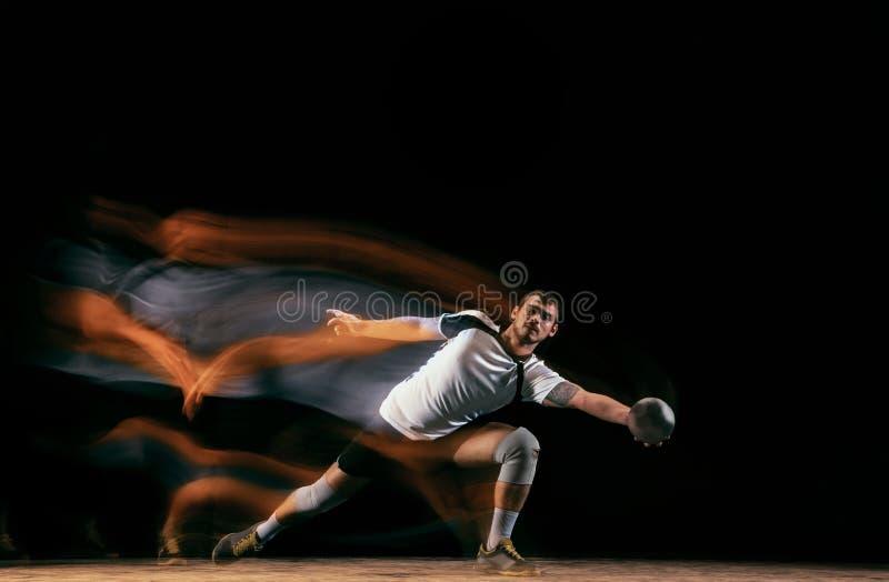 Jugador joven del balonmano contra fondo oscuro del estudio en luz mezclada foto de archivo