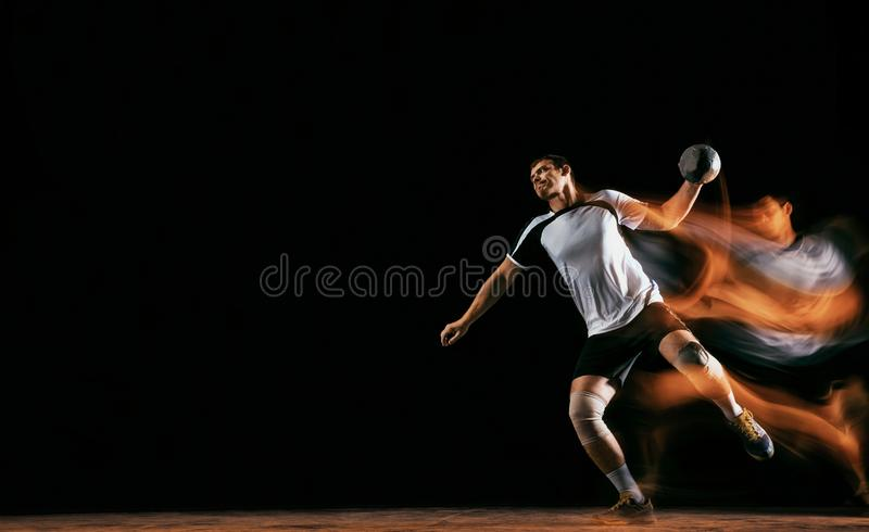 Jugador joven del balonmano contra fondo oscuro del estudio en luz mezclada imagenes de archivo
