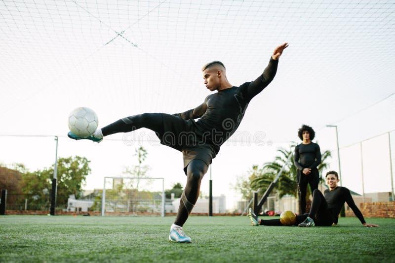 Jugador que golpea el balón de fútbol con el pie en campo imagenes de archivo
