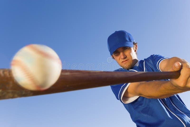 Jugador que golpea la bola con el bate de béisbol foto de archivo
