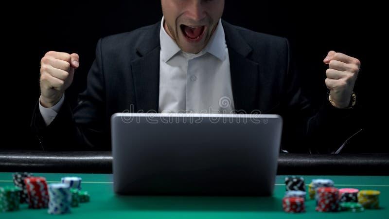 Jugador que juega en el ordenador portátil y que grita en el entusiasmo, apuesta que gana, fortuna foto de archivo libre de regalías