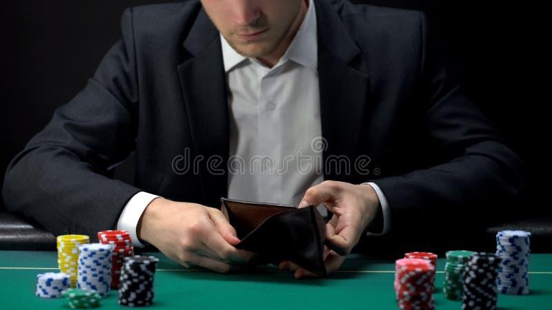Jugador trastornado que mira en cartera vacía, perdedor en la tabla del casino, apego del juego imagenes de archivo
