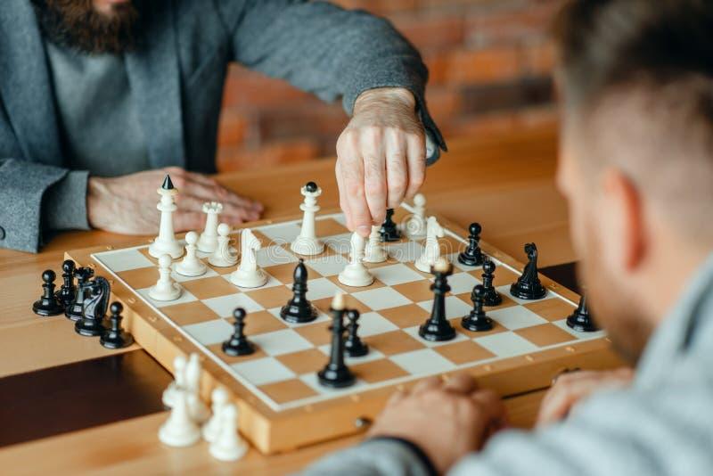 Jugadores de ajedrez masculinos que juegan, proceso de pensamiento imagen de archivo libre de regalías