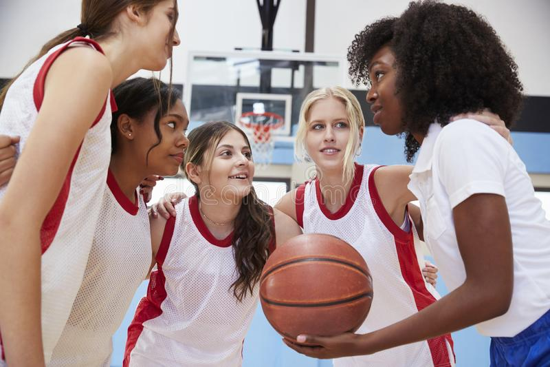 Jugadores de básquet de sexo femenino de la High School secundaria en el grupo que tiene Team Talk With Coach foto de archivo libre de regalías