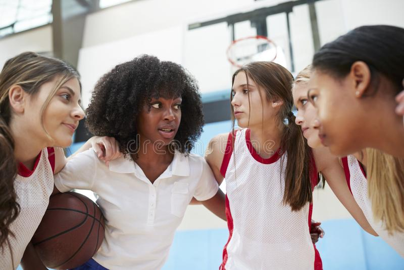 Jugadores de básquet de sexo femenino de la High School secundaria en el grupo que tiene Team Talk With Coach fotografía de archivo libre de regalías