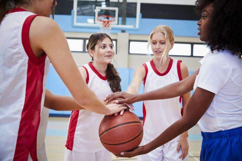 Jugadores de básquet de sexo femenino de la High School secundaria que se unen a las manos durante Team Talk With Coach foto de archivo libre de regalías