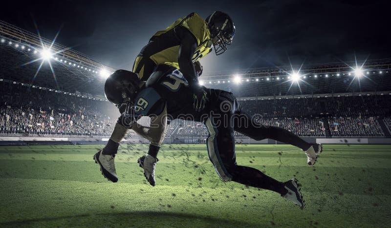 Jugadores de fútbol americano en la arena Técnicas mixtas fotografía de archivo