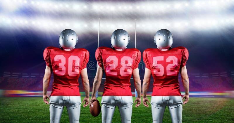 Jugadores de fútbol americano que se colocan con la bola de rugbi en estadio imágenes de archivo libres de regalías