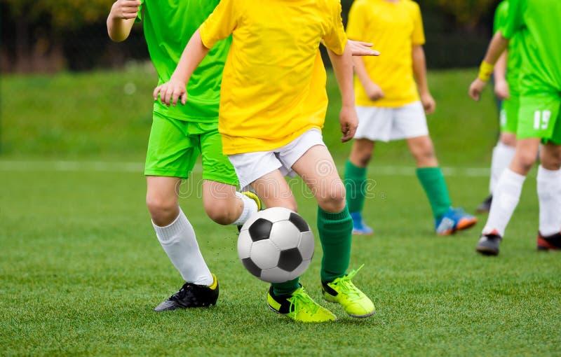Jugadores de fútbol corrientes del fútbol con la bola Futbolistas que golpean el partido de fútbol con el pie en la echada foto de archivo