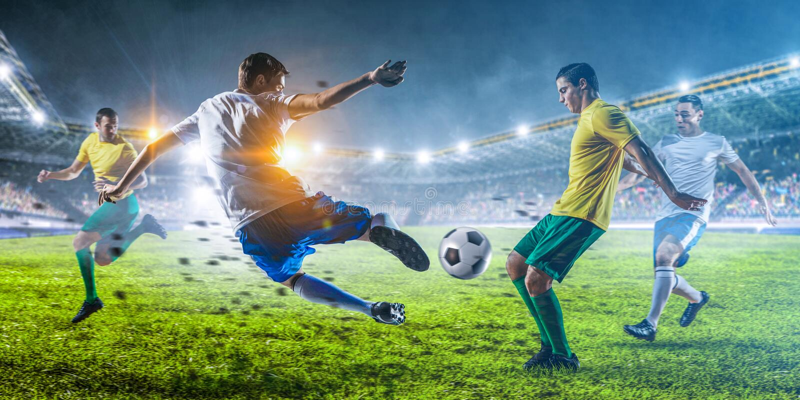 Jugadores de fútbol en la acción en un estadio fotos de archivo libres de regalías