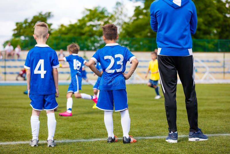 Jugadores de fútbol jovenes con el entrenador de fútbol foto de archivo libre de regalías