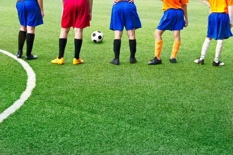 Jugadores de fútbol jovenes en academia del fútbol de la hierba del campo imagenes de archivo