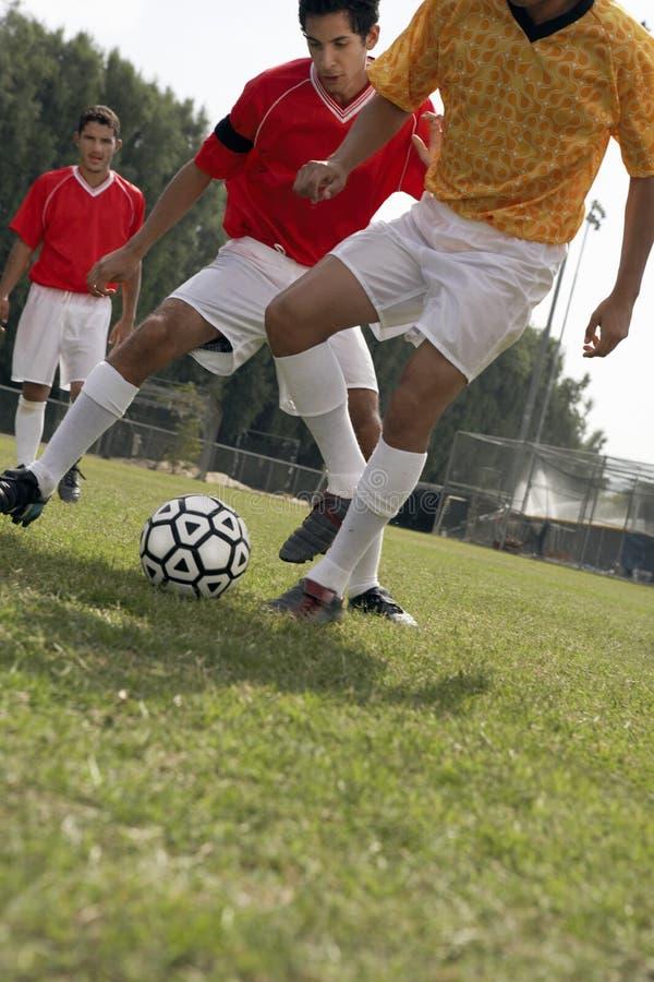 Jugadores de fútbol que compiten para la bola foto de archivo libre de regalías