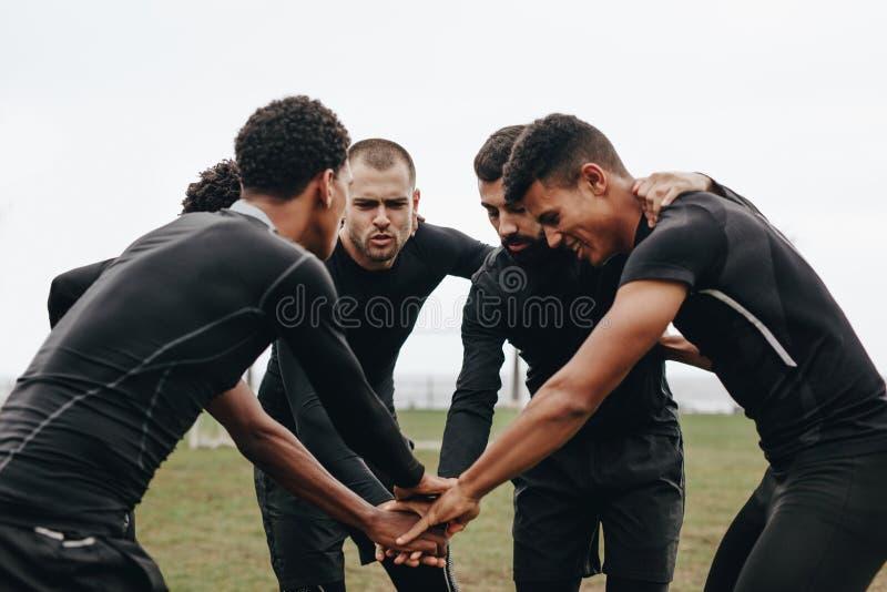 Jugadores de fútbol que se unen a las manos en el grupo que habla de la estrategia del juego Futbolistas que doblan adelante en u imagenes de archivo