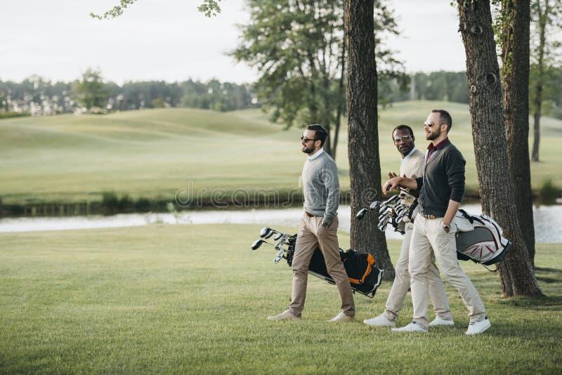 Jugadores de golf que celebran bolsos con los clubs de golf y que caminan en campo de golf imagen de archivo libre de regalías