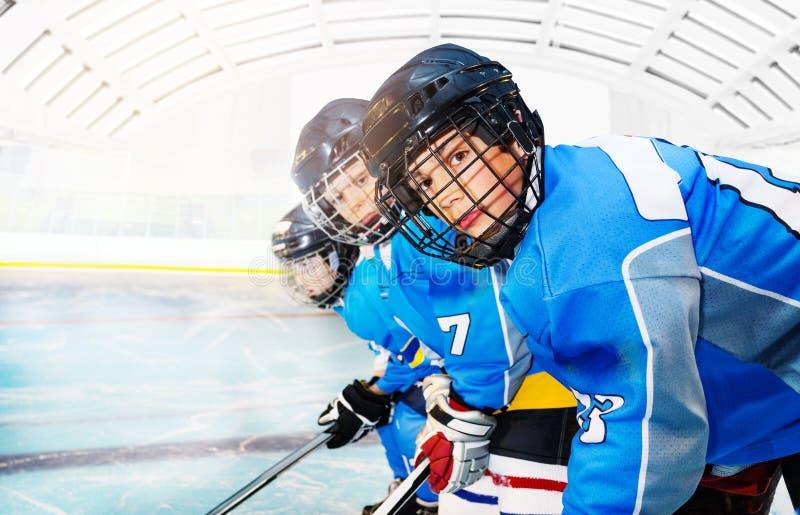 Jugadores de hockey jovenes que se colocan en línea en pista de hielo fotografía de archivo