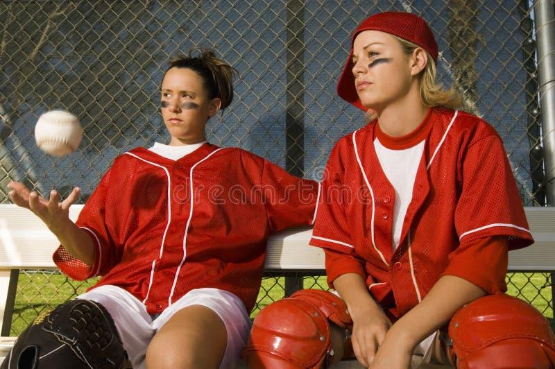 Jugadores de softball que se sientan en banco foto de archivo
