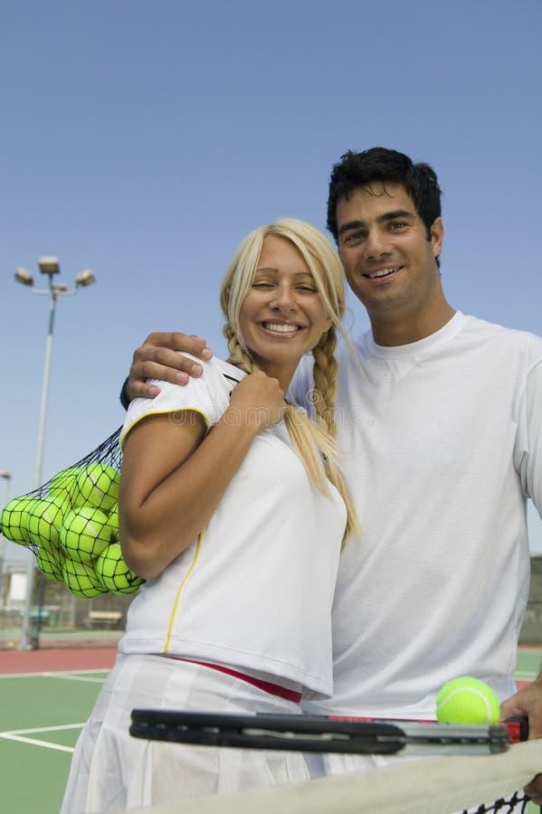 Jugadores de tenis de los dobles mezclados en el retrato del campo de tenis fotos de archivo
