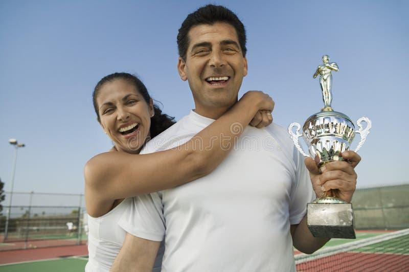 Jugadores de tenis de los dobles mezclados que se colocan en el campo de tenis que sostiene el retrato del trofeo fotografía de archivo