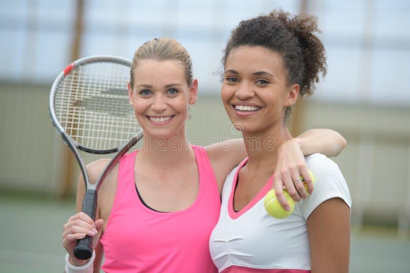 Jugadores de tenis de sexo femenino que juegan dobles en el campo de tenis fotos de archivo libres de regalías
