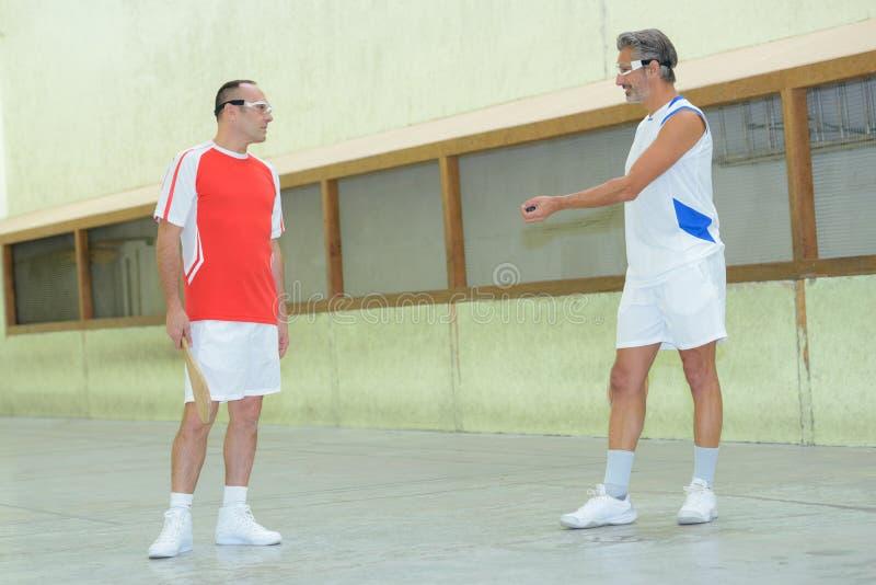Jugadores de tenis de la paleta que juegan en el muro de cemento foto de archivo libre de regalías