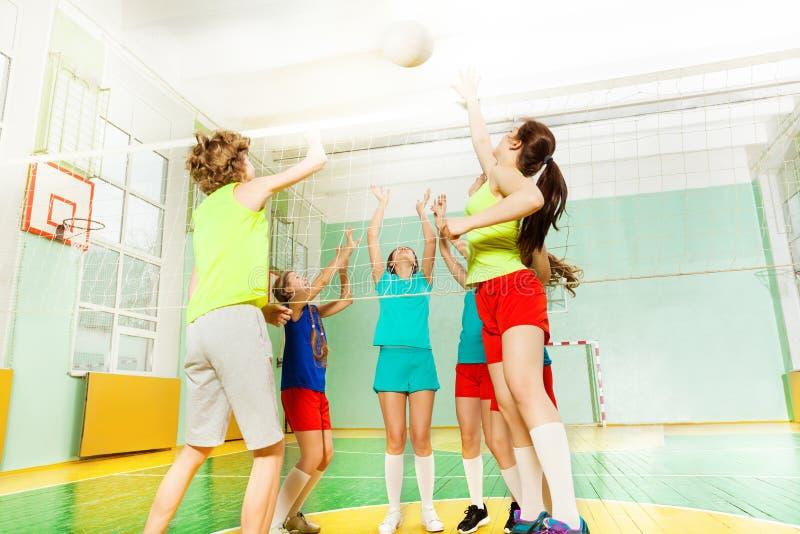 Jugadores de voleibol adolescentes que pegan la bola sobre red imagen de archivo libre de regalías