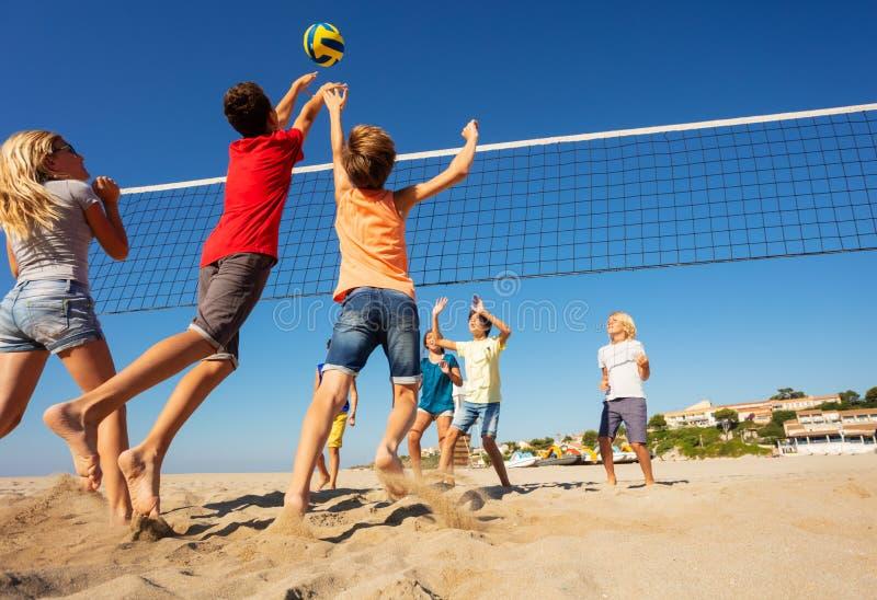 Jugadores de voleibol de playa que saltan para clavar la bola foto de archivo