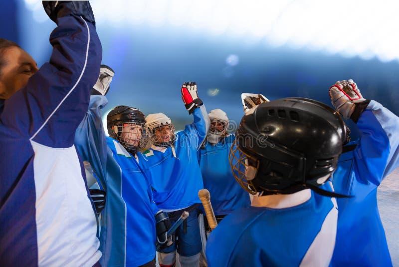 Jugadores del entrenador y de hockey que hacen alegría del equipo en pista imagen de archivo