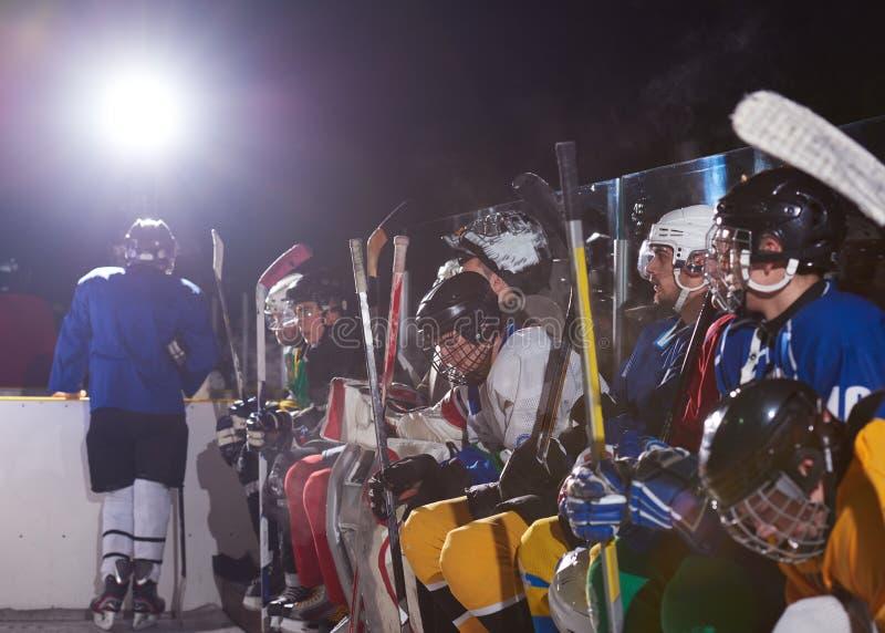 Jugadores del hockey sobre hielo en banco fotografía de archivo