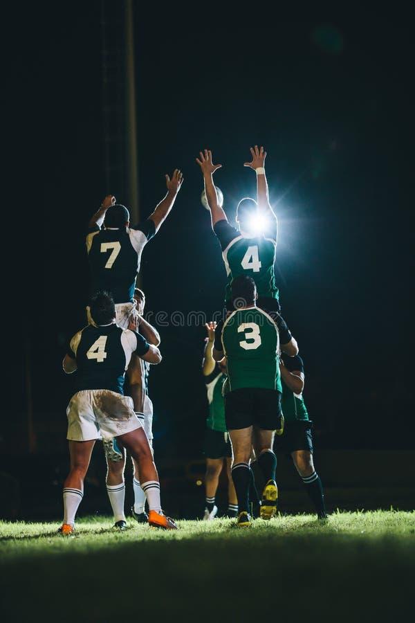 Jugadores del rugbi que saltan para la línea hacia fuera en el estadio imagen de archivo