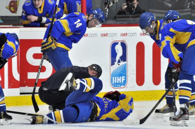 Jugadores doblados sobre el jugador de hockey herido imagen de archivo libre de regalías