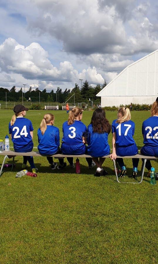 Jugadores substitutos del equipo de fútbol femenino que se sientan en un banco que mira el juego de torneo de la taza de Helsinki foto de archivo