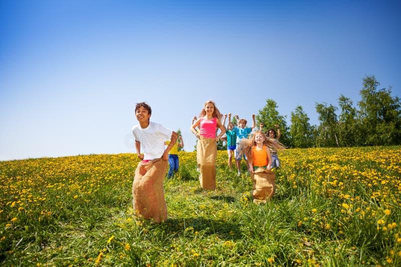 Jugando los niños saltan en sacos juntos imagenes de archivo