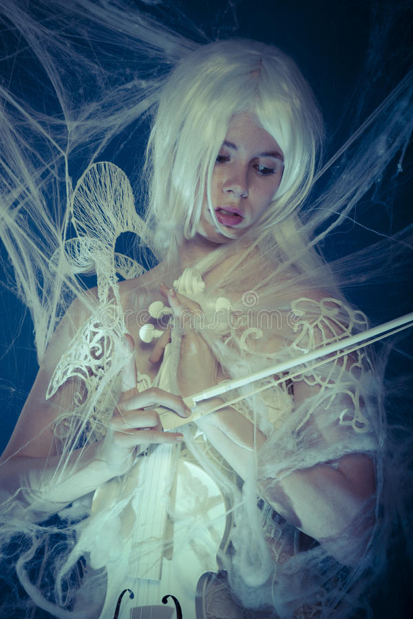 Jugando, violinista hermoso atrapado en un web de araña imagen de archivo