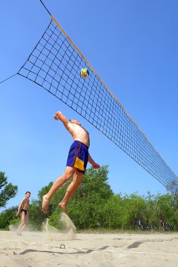 Jugando a voleibol de playa - el hombre gordo salta arriba para clavar la bola imagen de archivo